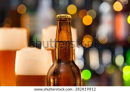 Bottle of beer with blur jugs on background - stock photo