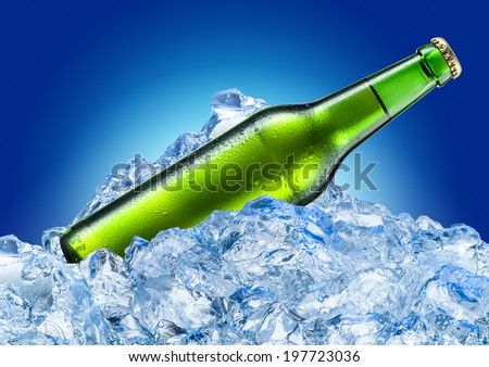 Bottle of beer with drops in ice cubes. Isolated on a blue.  - stock photo
