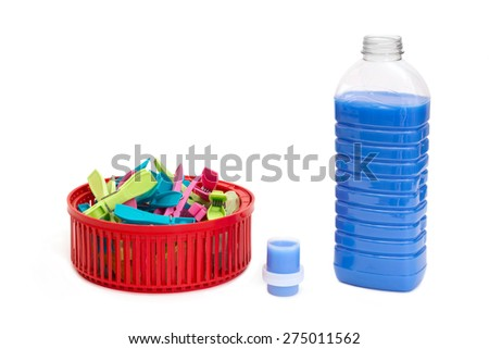 Bottle of blue laundry detergent near clothespins in a basket - stock photo