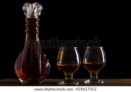 Bottle of brandy and two glasses on a wooden table top on a black - stock photo