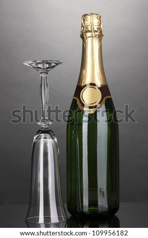 Bottle of champagne and goblet on grey background