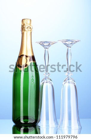 Bottle of champagne and goblets on blue background - stock photo