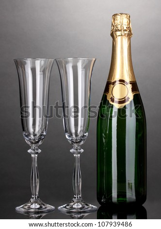 Bottle of champagne and goblets on grey background - stock photo