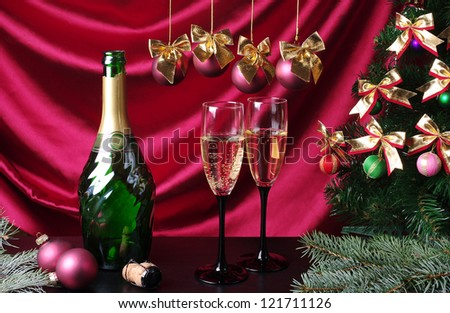 Bottle of champagne and two goblets on purple background. Happy New Year and Merry Christmas - stock photo
