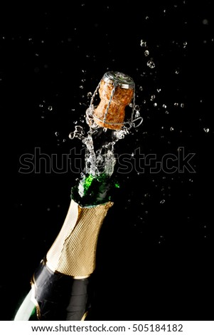 Bottle of champagne exploding isolated on black background