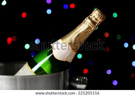 Bottle of champagne in bucket, on black background with color lights - stock photo
