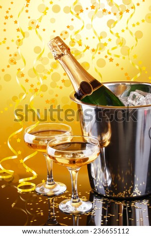 Bottle of champagne in bucket with ice and glasses of champagne, on bright background - stock photo
