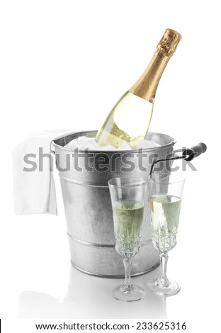 Bottle of champagne in metal ice bucket and two glasses isolated on white