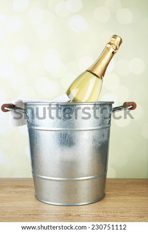 Bottle of champagne in metal ice bucket on wooden table on light background - stock photo