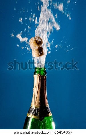 Bottle of champagne with a popping cork (against a blue background) - stock photo