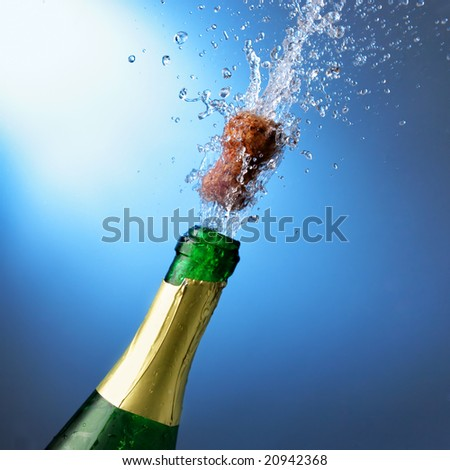 Bottle of champagne with splashes over blue background - stock photo