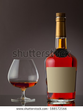 Bottle of cognac and glass - stock photo