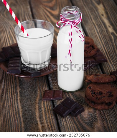 Bottle of cold milk with paper tube, chocolate cookies and chocolate on wooden background - stock photo