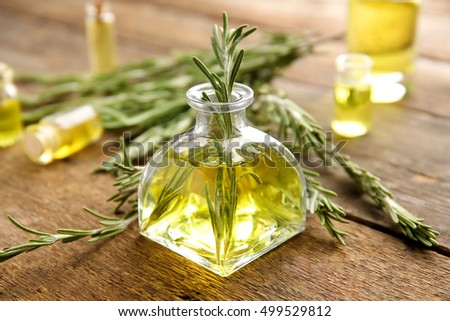Bottle of coniferous essential oil and rosemary branches on wooden background, close up view