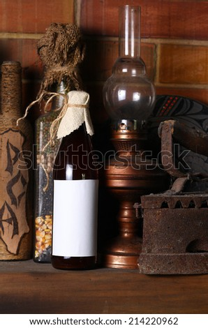 Bottle of craft beer with a blank label template standing on a fireplace shelf with various vintage objects