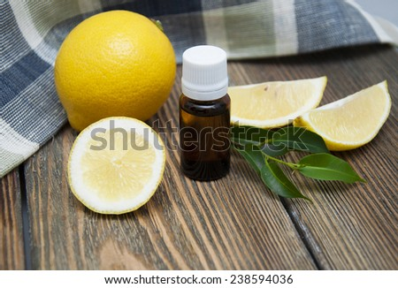 Bottle of essensial lemon oil with fresh organic fruit on a wooden background - stock photo