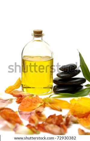 bottle of essential oil and black Stones balanced stones  with colorful flower plants