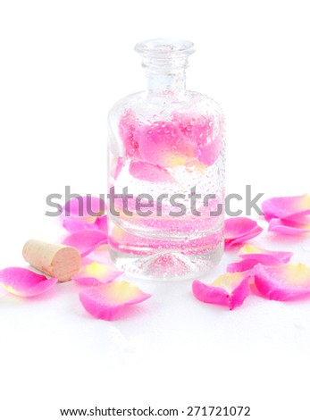Bottle of essential oil and petal pink rose isolated on white - stock photo