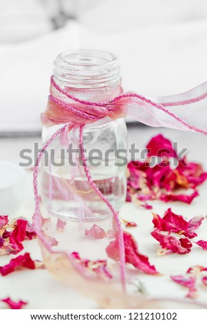 Bottle of essential oil and roses - stock photo