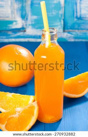 Bottle of freshly squeezed natural orange juice on bright blue surface - stock photo
