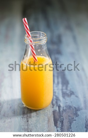 Bottle of Freshly squeezed orange juice sitting on a rustic wooden table. - stock photo