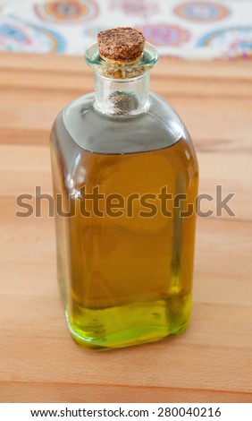 Bottle of golden olive oil on wood - stock photo