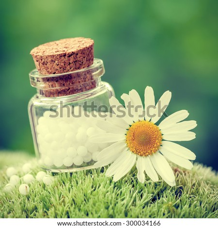 Bottle of homeopathy globules and daisy flower on green moss. Retro styled. - stock photo