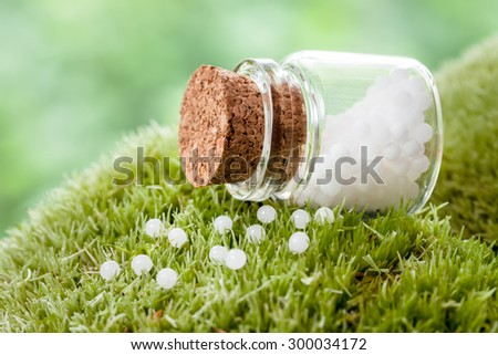 Bottle of homeopathy globules on green moss - stock photo