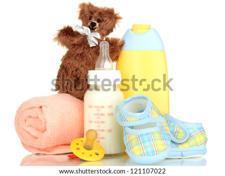 Bottle of milk, pacifier and baby cosmetic with towel isolated on white - stock photo