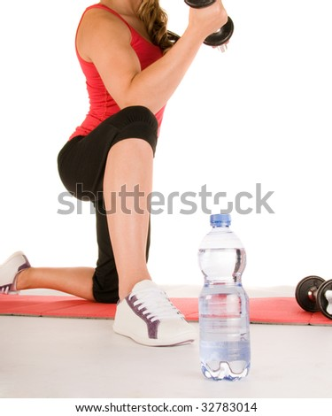 Bottle of mineral water in front of girl in the gym - stock photo
