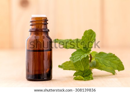 Bottle of mint essential oil on wooden background with selective focus. - stock photo