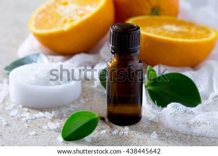 Bottle of orange essential oil aromatherapy and salt on brown stone background. Spa Orange. - stock photo