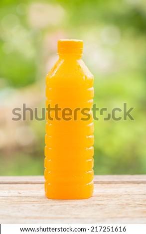 Bottle of orange juice on wood - stock photo