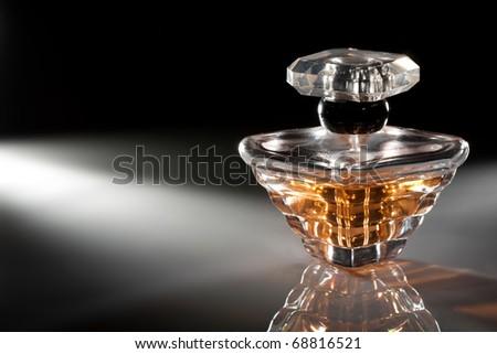Bottle of perfume on dark background - stock photo