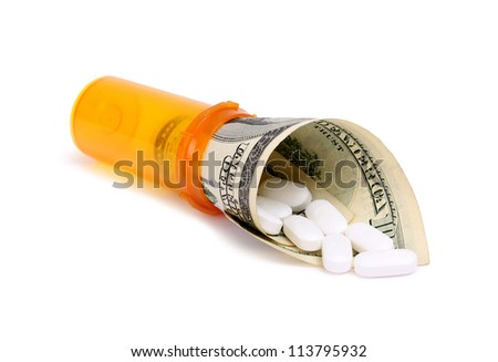 bottle of pills and money isolater on white - stock photo