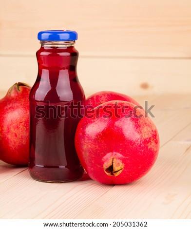 Bottle of pomegranate juice with pomegranates. Whole background. - stock photo