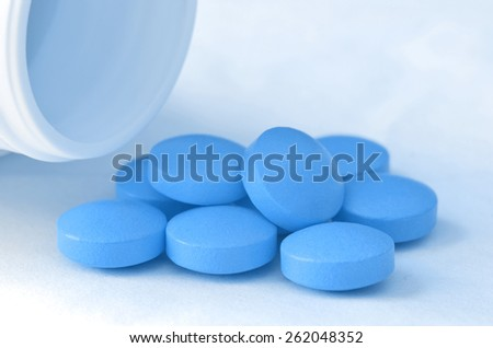 Bottle of pour out blue pills of drugs on white background