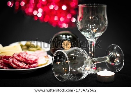 Bottle of red dry wine with wineglasses and candle on a celebratory table. Colorful bokeh background. Image with dark vignette effect - stock photo