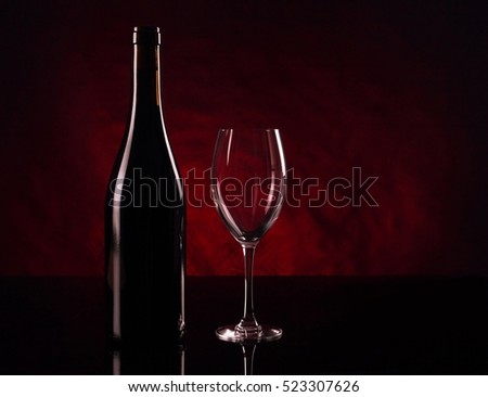 Bottle of red vine and empty wineglass