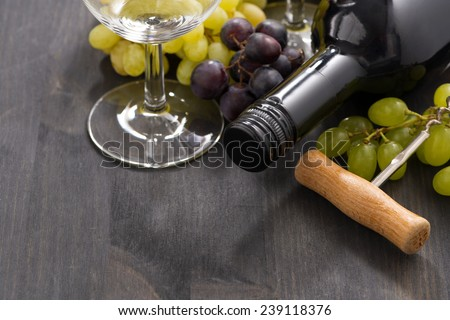 bottle of red wine and grapes on a wooden background, close-up, horizontal - stock photo