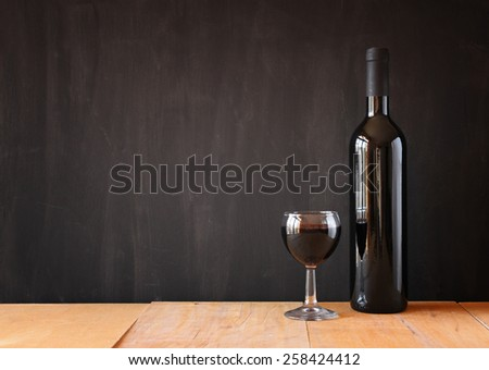 bottle of red wine and wine glass over wooden table.