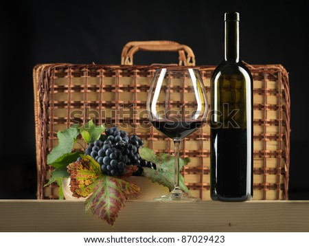 bottle of red wine, glass, grapes and picnic basket on black background - stock photo