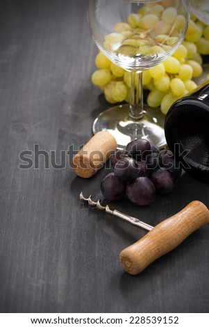 bottle of red wine, grape and corkscrew on a wooden background, vertical, close-up - stock photo