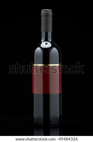 Bottle of red wine on a table with black background - stock photo