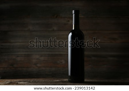 Bottle of red wine on grey wooden background - stock photo
