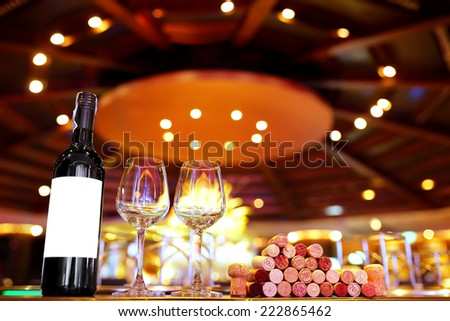 Bottle of red wine wine glasses and corks on wooden table - stock photo