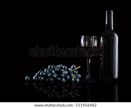 bottle of red wine,  wine glasses and grapes on a black  background