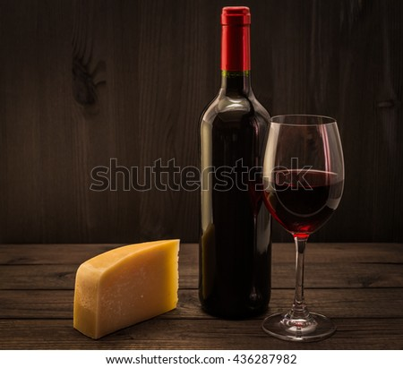 Bottle of red wine with a glass of red wine and a piece of parmesan on an old wooden table