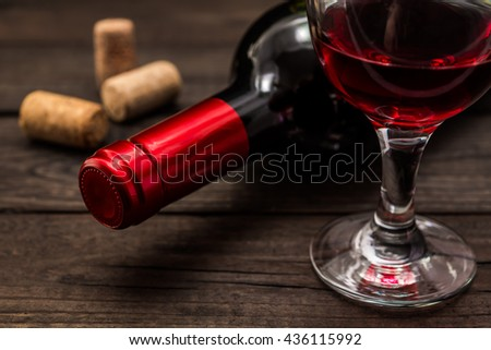 Bottle of red wine with a glass of red wine and corks on an old wooden table. Close up view, focus on the bottle of red wine - stock photo