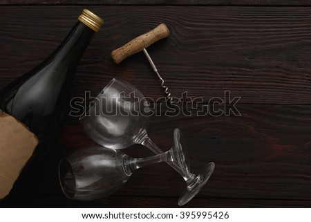Bottle of red wine with blank label next to to two empty glasses with corkscrew on wooden table. Flat lay, above view, copy space,Chiaroscuro styled